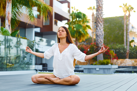 siddhasana: Meditation for Less Stress. Young beautiful woman sitting outdoors in lotuse posture.