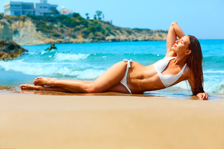 Sexy young woman with long legs and fit body sunbathing on the beach in white bikini. Vacations in Cyprus , Greece. Stock Photo