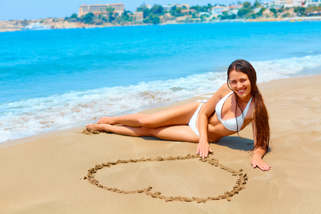 girl legs: Heart shape is drawn in the sand. Girl is enjoying summer , wearing white bikini. Summer honeymoon vacation.