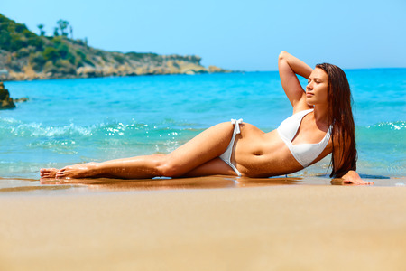 sexually: Beautiful girl with long legs and fit body lying on the beach in white bikini. Spa, skincare, relaxation, depilation.