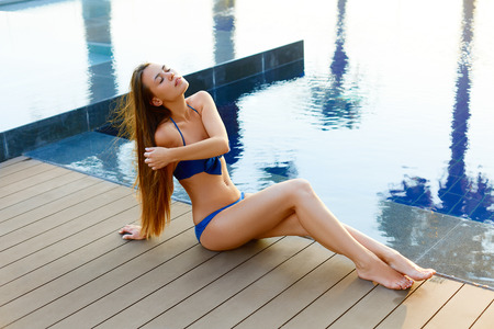 woman in bath: Spa and skincare procedures in summer. Beautiful young girl with healthy tanned skin and long natural hair enjoying summer in spa and resort hotel. Stock Photo