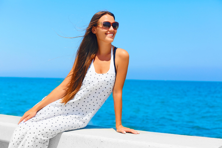 summer dress: Young beautiful woman with long hair enjoying summer. Blue Mediterranean Sea View on background. Stock Photo