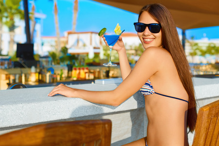 Summer party. Sexy young woman with long hair drinking cocktail at the beach bar in bikini and sunglasses. 스톡 콘텐츠