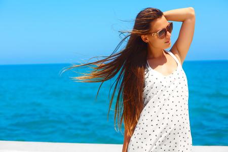 mujer alegre: vacaciones de verano. Mujer joven en el vestido blanco y gafas de sol está caminando sobre un muelle junto al mar. Foto de archivo