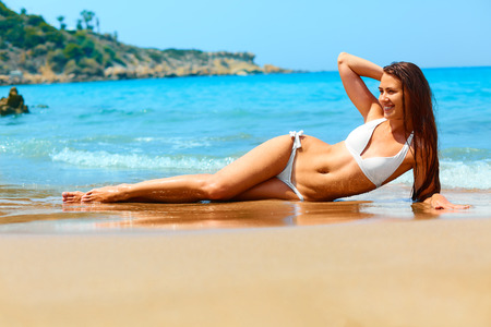 lying on stomach: Happy sexy woman with long legs and fit body lying on the beach in white bikini. Spa, skin care and relaxation. Vacations in Cyprus , Greece. Stock Photo
