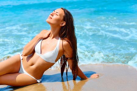 sonnenbaden: Glückliche Frau mit dem langen Haar und gesunde strahlende Haut Entspannung am Strand im weißen Bikini.