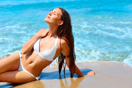 lying on stomach: Happy woman with long hair and healthy glowing skin relaxing  on a beach in white bikini.