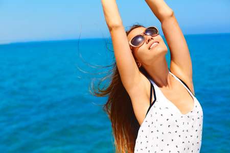 Summer vacation. Happy woman enjoying the sun. She's wears white dress and dark sunglasses. She feels relaxed, happy, healthy and free. Standard-Bild