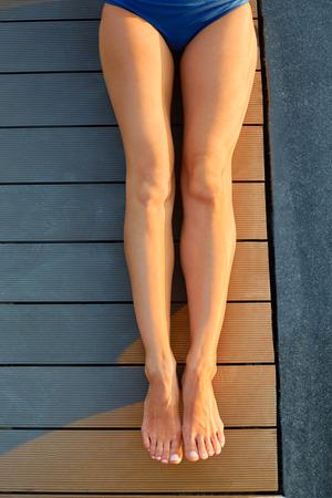sexy füsse: Schöne lange schlanke weibliche Beine Sonnenbaden. Junge Frau mit enthaart, Cellulite frei, gebräunte Beine im Freien entspannen und genießen Sommerurlaub.