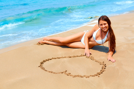 dream body: Romantic young woman in white bikini is lying on the beach, smiling and drawing a heart shape  on the sand. Honeymoon vacation.