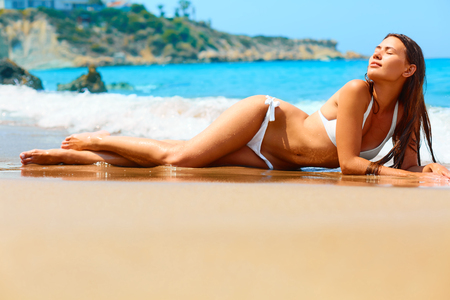 sexually: Summer vacation. Beautiful healthy young girl in white bikini is enjoying the sun on the beach while lying on wet sand. She uses sunscreen lotions because she takes care of her skin. Stock Photo