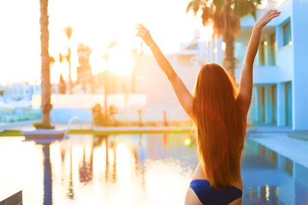straight up: Freedom and happiness. Sexy young woman with long hair feeling free and happy near the pool. Stock Photo