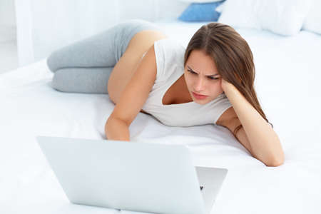 looking at computer: Depressed Pregnant Woman Works at Laptop Computer While Lying on a Bed Stock Photo