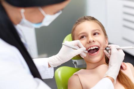 dientes: Chequeo de los dientes en el consultorio del dentista. Dentista examinar niñas dientes en la silla de los dentistas