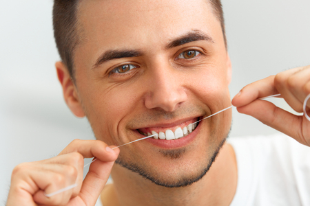 Closeup of young man flossing his teeth. Cleaning teeth with dental floss