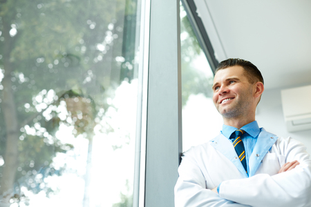 thinks: Dentist Doctor Stands Near Window and Thinks about Clinic Future