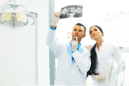 x ray image: Dentist and female assistant are discussing dental X Ray image Stock Photo
