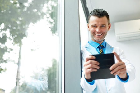 takes: Dentist Doctor Takes Photo Using His Smartphone. Doctor Has Some fun Stock Photo