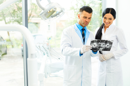Dentist and female assistant are discussing dental X Ray image Stock Photo
