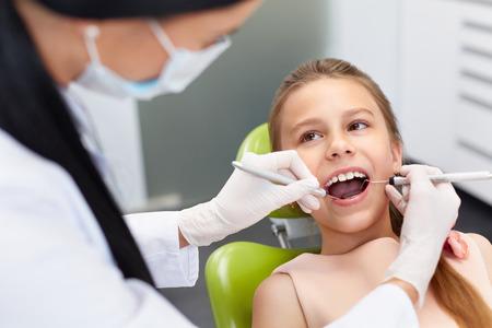 Chequeo de los dientes en el consultorio del dentista. Dentista examinar niñas dientes en la silla de los dentistas Foto de archivo
