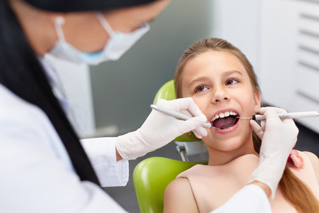 Teeth checkup at dentist's office. Dentist examining girls teeth in the dentists chair Stock Photo