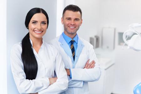 歯科医院で歯科医のチーム。自分の職場で 2 人の笑みを浮かべて医師