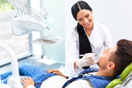 Famele dentist and man in dentists office.  Dentist and Patient