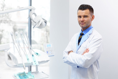 dentista: Dentista M�dico retrato. Hombre joven en su lugar de trabajo. Cl�nica dental