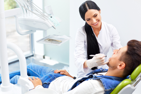 dentists: Famele dentist and man in dentists office.  Dentist and Patient