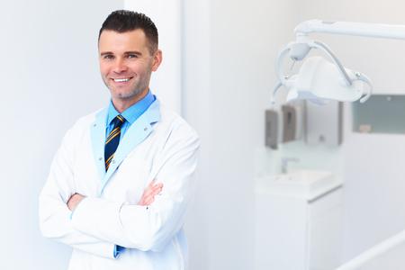 dentista: Dentista Médico retrato. Hombre joven en su lugar de trabajo. Clínica dental
