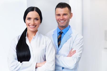 dentist: Dentista del equipo en la Clínica Dental. Dos médicos sonriendo a su lugar de trabajo Foto de archivo