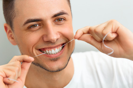 dental floss: Closeup of young man flossing his teeth. Cleaning teeth with dental floss