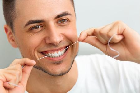 dientes sanos: Primer del hombre joven hilo dental sus dientes. Limpieza de los dientes con hilo dental Foto de archivo