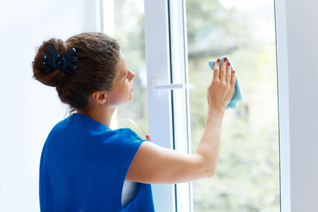 mujer limpiando: Mujer joven que limpia la ventana de vidrio. Empresa de limpieza Trabajador