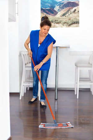 mopping: Portrait Of Young Woman Mopping Floor At Home . Cleaning Sevice