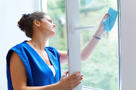 personal de limpieza: Mujer atractiva que lava la ventana. trabajador de la limpieza de la empresa de trabajo Foto de archivo
