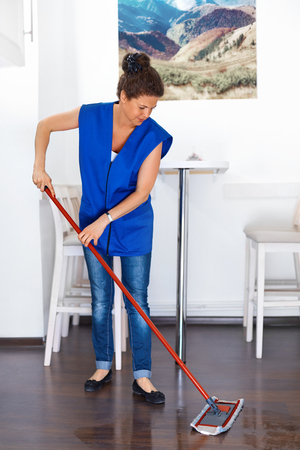 cleaning service: Portrait Of Young Woman Mopping Floor At Home . Cleaning Sevice