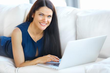 usando computadora: Mujer joven que usa un ordenador portátil mientras se relaja en el hogar