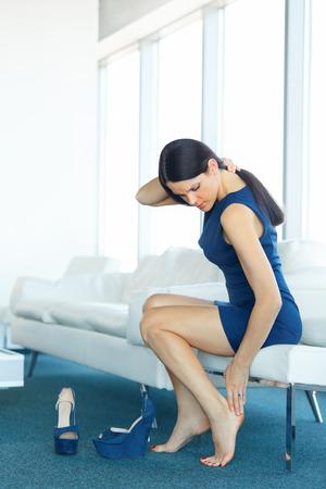 piernas con tacones: Dolor de pie. Joven mujer Masaje Sus Piernas Cansadas