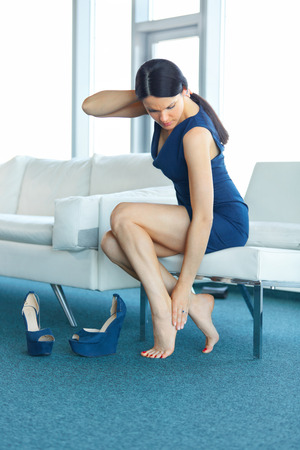 painful: Foot pain. Young Woman Massage Her Tired Legs