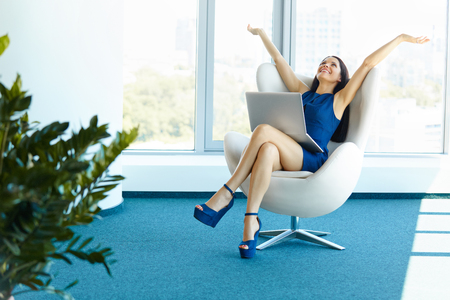 successful business woman: Business woman celebrates successful deal at office. Bussiness People