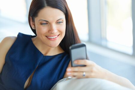 busy person: Business Woman Using Her Smartphone at The Office Stock Photo