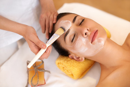 cremas faciales: Cara Tratamiento. Mujer en salón de belleza Obtiene Máscara Marina Foto de archivo