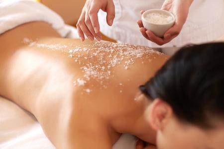 massieren: Spa Frau. Brunette Getting ein Salzpeeling Kosmetische Behandlung im Health Spa. Body Scrub.