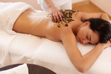 spa beauty: Spa Woman. Brunette Getting a Marine Algae Wrap Treatment in Spa Salon