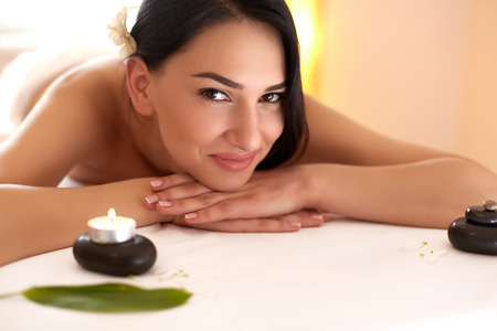 woman relaxing: Spa Massage. Beautiful Brunette Gets Spa Treatment in Salon. Stock Photo