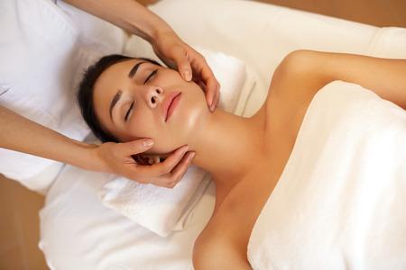 carita feliz: Masaje de cara. Primer plano de una mujer joven que consigue Tratamiento de spa. Foto de archivo