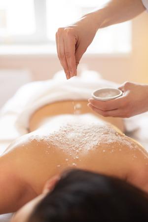 scrub: Spa Woman. Brunette Getting a Salt Scrub Beauty Treatment in the Spa. Body Scrub. Stock Photo