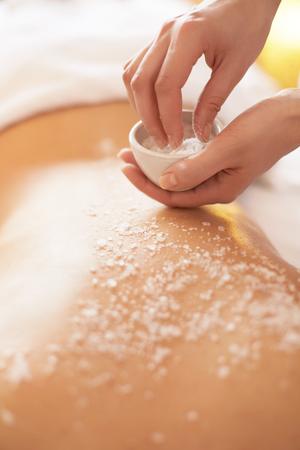tratamientos corporales: Spa mujer. Brunette Conseguir un tratamiento de belleza sal Scrub en el Spa. Exfoliación corporal. Foto de archivo