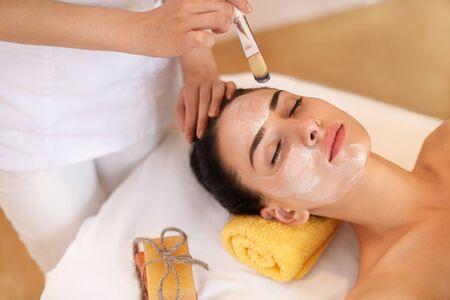 salon de belleza: Cara Tratamiento. Mujer en salón de belleza Obtiene Máscara Marina Foto de archivo